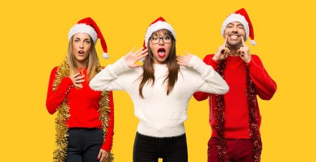 Un gruppo di persone donna bionda vestita per le vacanze di natale sorpreso e scioccato.