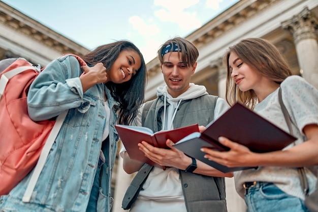 Un gruppo di studenti si prepara per l'esame e legge gli appunti del libro per strada vicino al campus universitario.