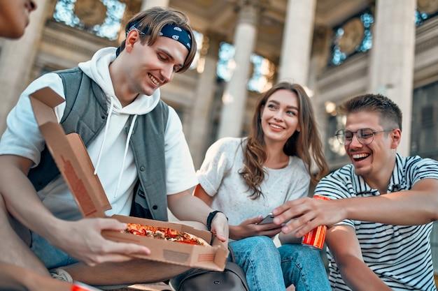 Un gruppo di studenti si siede sui gradini fuori dal campus e mangia pizza e soda