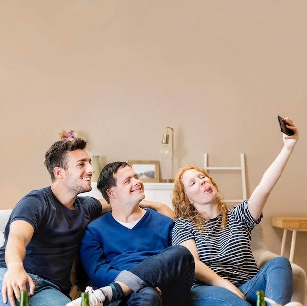 Un gruppo di tre amici a casa che prendono un selfie