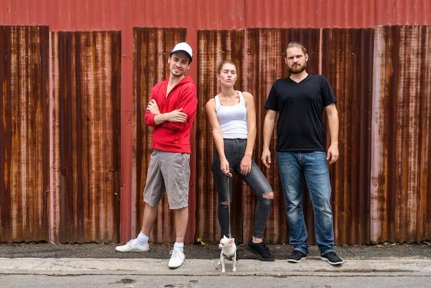 Un gruppo di tre amici contro il muro di ferro arrugginito nelle strade all'aperto