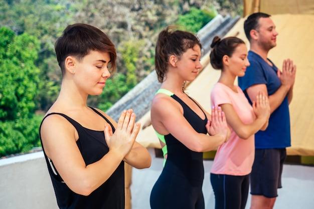 Un gruppo di tre belle donne e un uomo che praticano yoga nella meditazione di gruppo