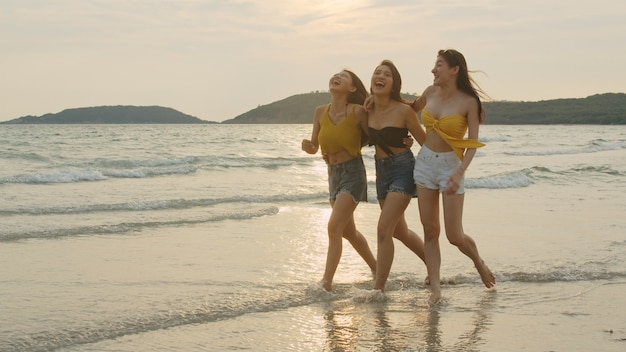 Un gruppo di tre giovani donne asiatiche che corrono sulla spiaggia
