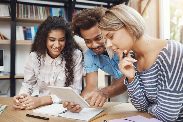 Un gruppo di tre giovani startuper di bell'aspetto seduti in uno spazio di coworking leggero, parlando del progetto futuro, guardando attraverso esempi di design su tavoletta digitale. amici sorridenti, parlando di lavoro.
