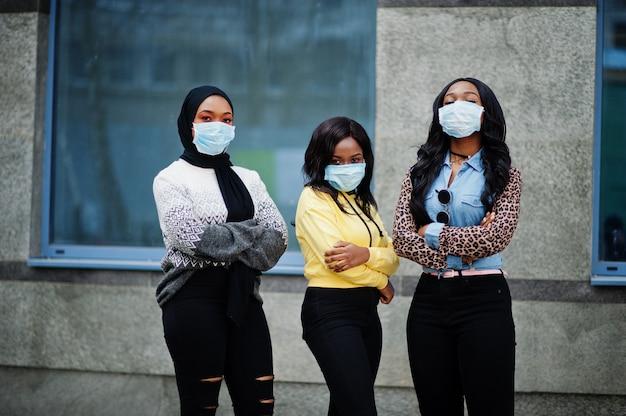 Un gruppo di tre giovani volontari afroamericani che indossano la maschera di protezione all'aperto. quarantena del coronavirus e pandemia globale.