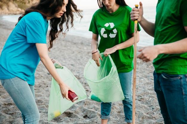 Un gruppo di tre volontari che raccolgono rifiuti in spiaggia