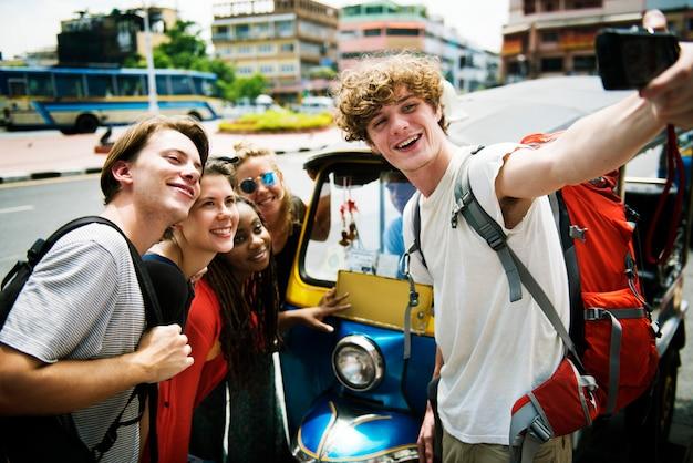 Un gruppo di turisti caucasici prendendo selfie di fronte a un tuk tuk