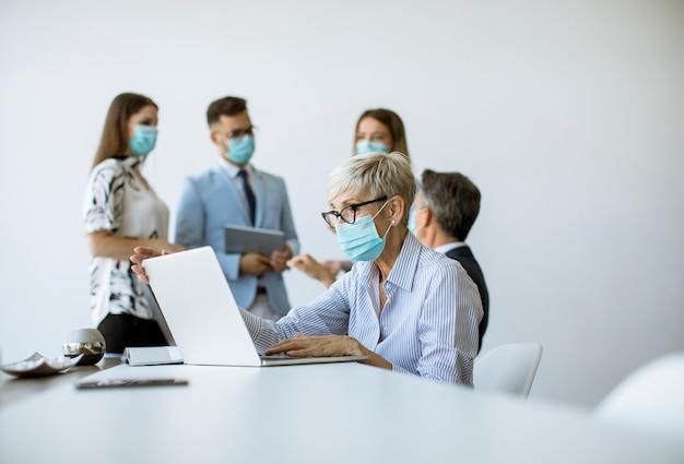Un gruppo di uomini d'affari ha una riunione e lavora in ufficio e indossa maschere come protezione dal coronavirus