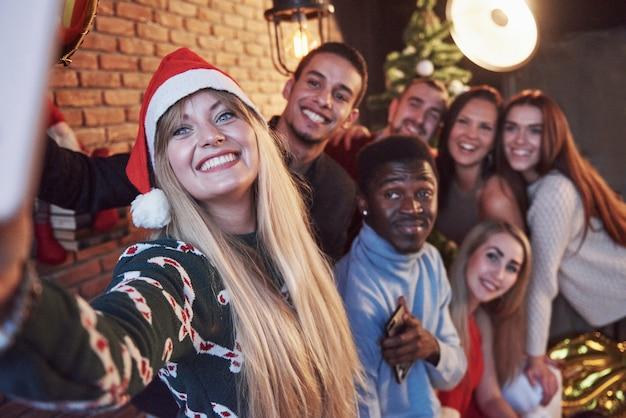 Un gruppo di vecchi amici allegri comunica tra loro e fa una foto selfie. il nuovo anno sta arrivando. festeggia il nuovo anno in un'atmosfera accogliente