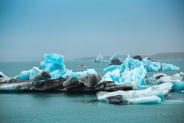 Un gruppo di viaggiatori prende una barca per vedere il ghiaccio galleggiante nell'oceano iceberg a jokulsarlo