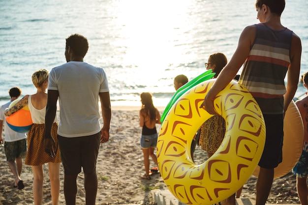 Un gruppo eterogeneo di amici che cammina verso la spiaggia con tubi gonfiabili