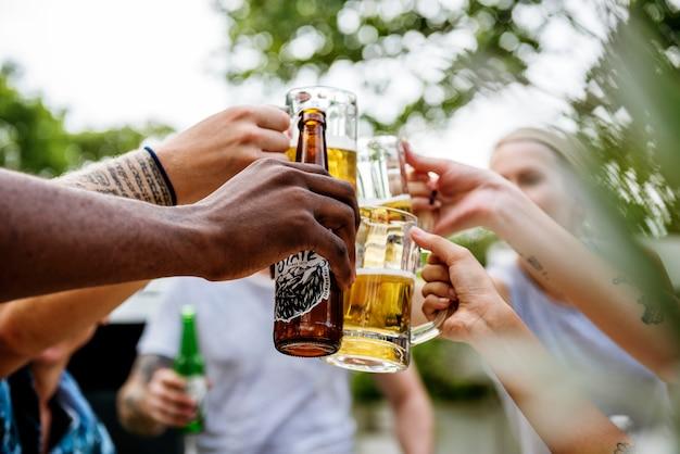 Un gruppo eterogeneo di amici che festeggiano e bevono birre