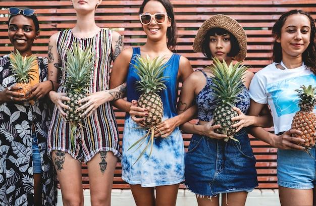 Un gruppo eterogeneo di donne in piedi e tenendo insieme l'ananas