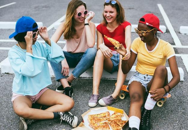 Un gruppo eterogeneo di donne sedute sul pavimento e mangiando pizza insieme
