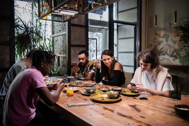 Un gruppo multietnico di studenti che mangiano in un moderno caffè con internet wifi gratuito