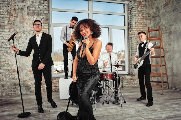 Un gruppo musicale multirazziale si esibisce in uno studio di registrazione. un gruppo di musicisti internazionali che provano una performance di concerto. cantante, montone, chitarrista