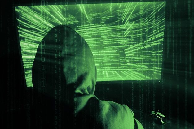 Un hacker uomo in un cappuccio in una stanza buia
