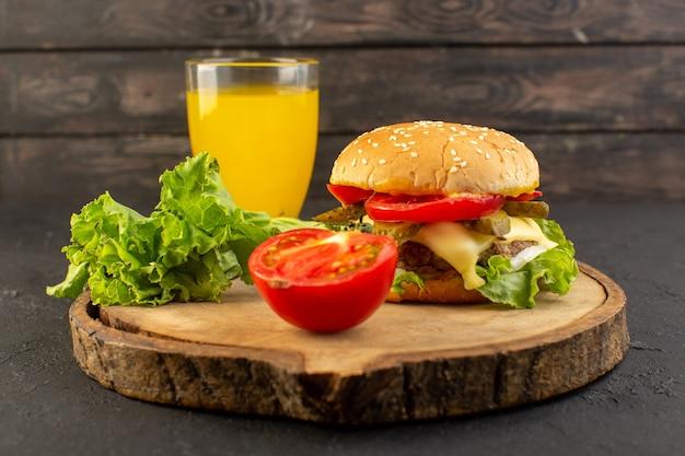 Un hamburger di pollo con vista frontale con formaggio e insalata verde insieme a succo sulla scrivania in legno e panino cibo pasto veloce