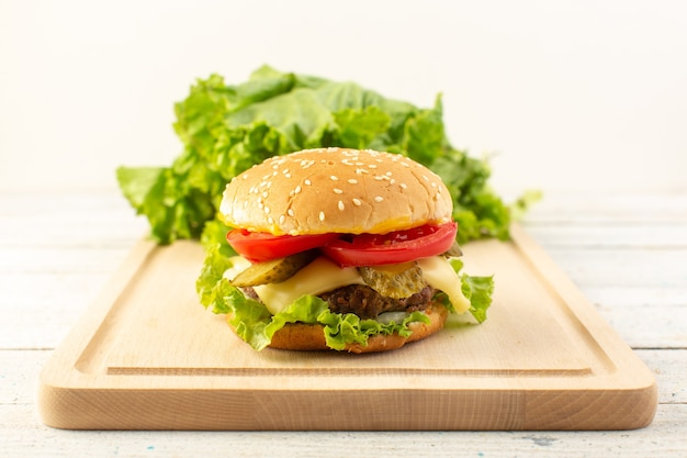 Un hamburger di pollo vista frontale con formaggio e insalata verde sullo scrittorio di legno e pasto fast-food sandwich