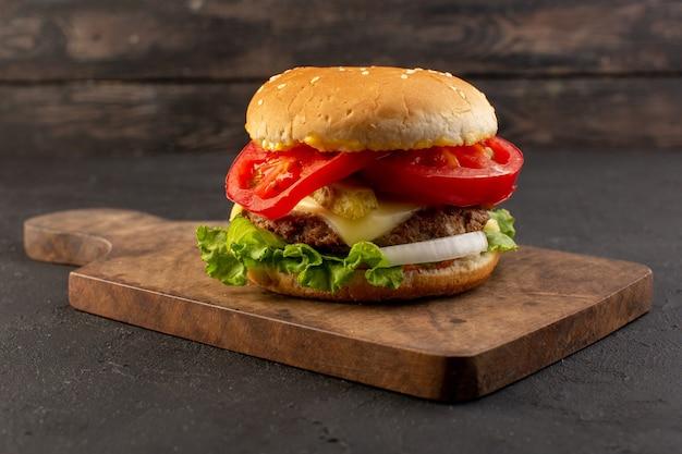 Un hamburger di pollo vista frontale con formaggio e insalata verde sullo scrittorio di legno e superficie grigia
