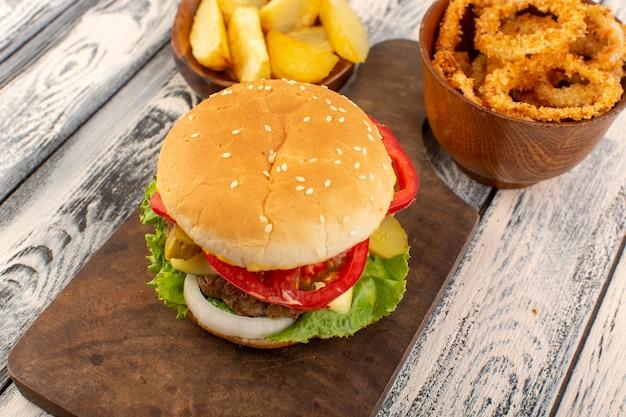 Un hamburger di pollo vista frontale con formaggio e patate insalata verde sullo scrittorio di legno e superficie grigia