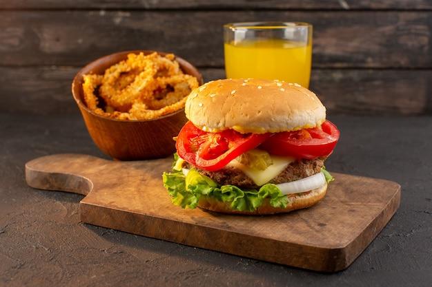 Un hamburger di pollo vista frontale con insalata di formaggio verde e succo di frutta sulla scrivania in legno e un pasto fast-food sandwich