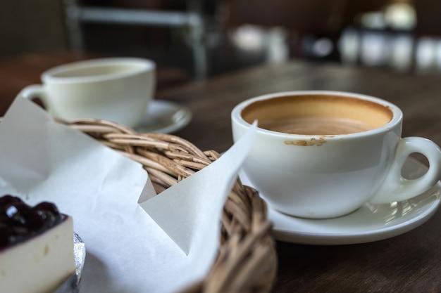 Un'immagine del primo piano di due tazze di caffè e una merce nel carrello del dolce sulla tavola di legno d'annata in caffè