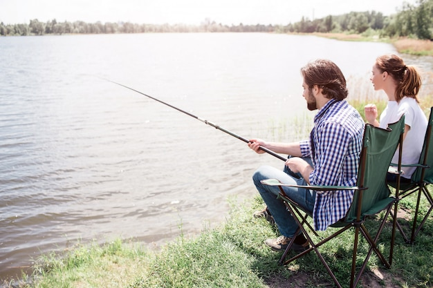 Un'immagine dell'uomo adulto e della donna che si siedono alla riva del fiume in questo giorno soleggiato bello e bello. guy sta cercando di catturare alcuni pesci. entrambi guardano verso l'acqua.