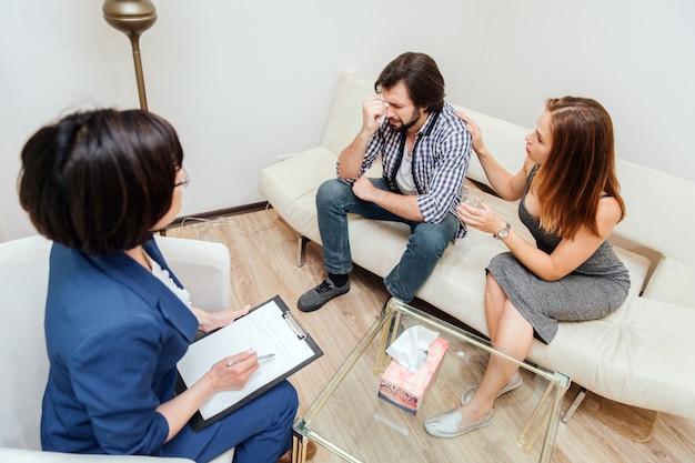 Un'immagine dell'uomo turbato che si siede sul sofà con sua moglie. lui sta piangendo. la giovane donna sta cercando di calmarlo. tiene in mano una tazza d'acqua. l'altra mano sdraiata sulla sua spalla.
