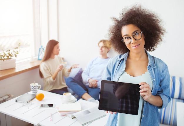 Un'immagine della ragazza afroamericana sta stando e guardando. lei sorride e tiene in mano una tavoletta nera. le sue amiche sono sedute sul divano e parlano tra loro.