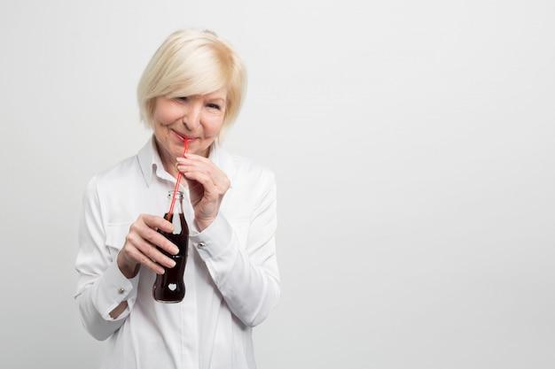 Un'immagine di donna moderna e allegra che ama bere di tanto in tanto la cola. è un'abitudine che ha dalla sua infanzia. non è salutare e una brutta cosa da fare.