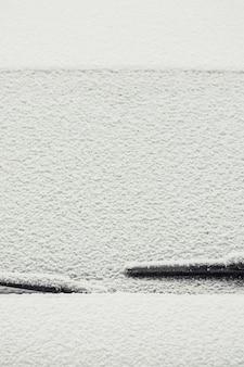 Un'immagine di sfondo minimalista del parabrezza dell'auto coperto da uno strato di neve.