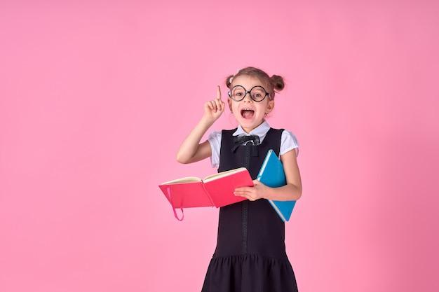 Un'immagine di una scolara con il libro di testo che indovina emotivamente indicando qualcosa sopra l'isolato lo spazio rosa