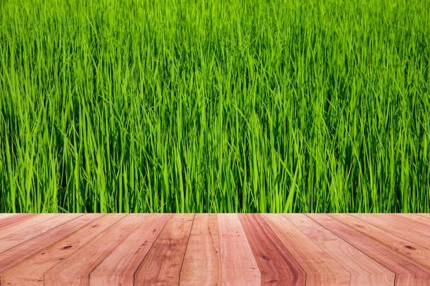 Un'immagine di uno scrittorio di legno davanti ad una priorità bassa astratta di riso verde.