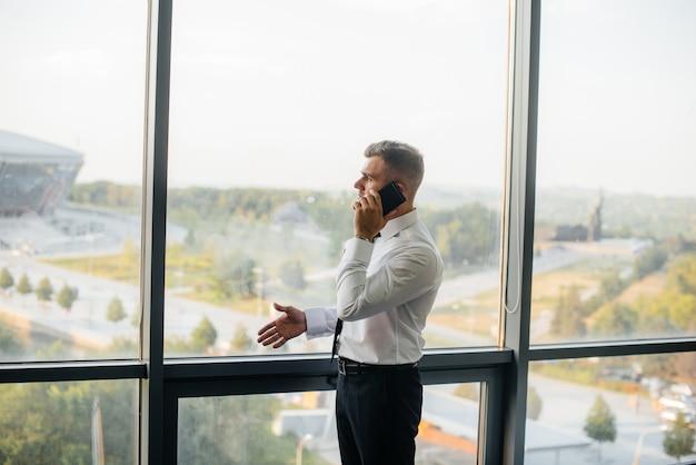 Un impiegato in ufficio è in piedi vicino alla finestra. finanza