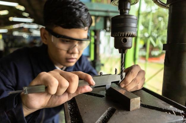 Un industriale dell'ingegnere dell'uomo che porta il cappello duro lavora alle calibri a nonio di factory.using.