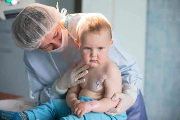Un'infermiera di un ragazzino tratta un'ustione. un bambino in ospedale è ferito. il medico tratta il bambino. piccolo paziente ricoverato.
