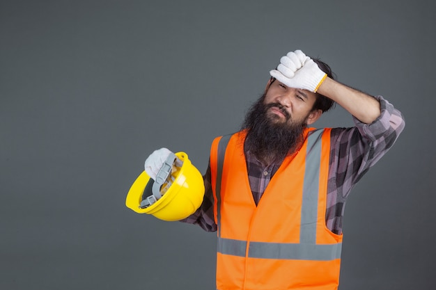 Un ingegnere che indossava un elmetto giallo con guanti bianchi mostrò un gesto su un grigio.