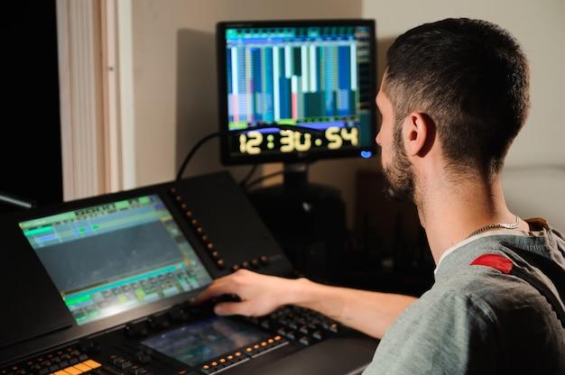 Un ingegnere dell'illuminazione lavora con il controllo dei tecnici delle luci