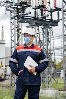 Un ingegnere della sottostazione elettrica ispeziona le moderne apparecchiature ad alta tensione in una maschera al momento della pissemia. energia. industria.