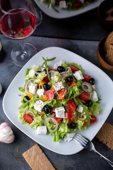 Un'insalata della grecia di vista superiore ha affettato il vino rosso delle olive dentro il piatto bianco