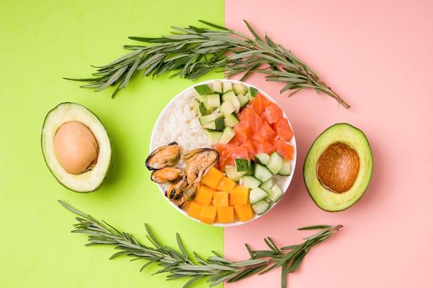 Un'insalata di poke tradizionale hawaiana su uno sfondo rosa e verde accanto a semi di avocado e cumino.