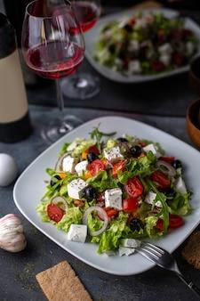 Un'insalata di verdure affettata dell'insalata della grecia di vista frontale con i pomodori cetrioli formaggio bianco e olive dentro le verdure bianche di vitamine del piatto