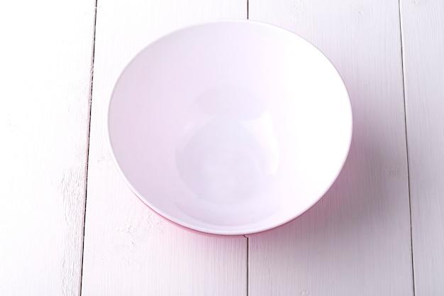 Un'insalatiera rossa vuota sulla tavola di legno bianca
