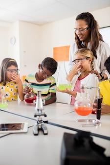 Un insegnante che guarda gli alunni fare scienza