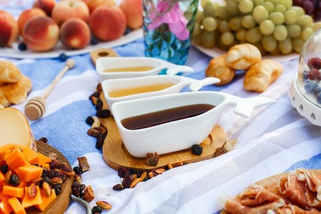 Un insieme di tre salsiere bianche con miele dolce sul vassoio di legno all'alimento di picnic presenta il fondo