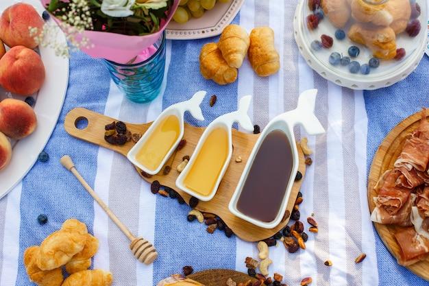 Un insieme di tre sauceboats bianchi con miele dolce sul vassoio di legno all'alimento di picnic presenta il fondo