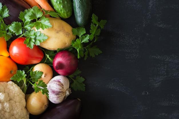 Un insieme di verdure fresche cetrioli, pomodori, cavoli, carote, aglio, cipolle, patate su un nero. copyspace