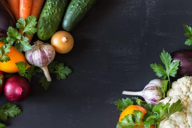 Un insieme di verdure fresche cetrioli, pomodori, cavoli, carote, aglio, cipolle su un nero. copyspace
