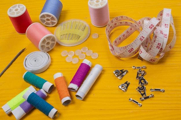 Un kit da cucito, ago, filo, ago, posizionato su un pavimento di legno giallo.